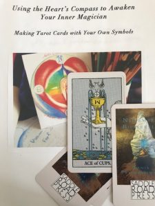 heart's compass with candle aflame in center, ace of cups held in hand, and Draft Book Cover: Using the Heart's Compass to Awaken Your Inner Magician