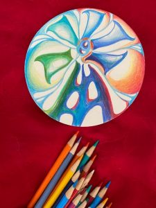 rainbow windmill with colored pencils below it on red backdrop